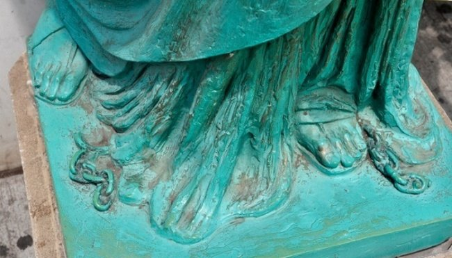 2. The broken chain at the feet of the Statue of Liberty